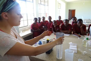 A GEC volunteer does an experiment with Kitenga students to clean dirty water.