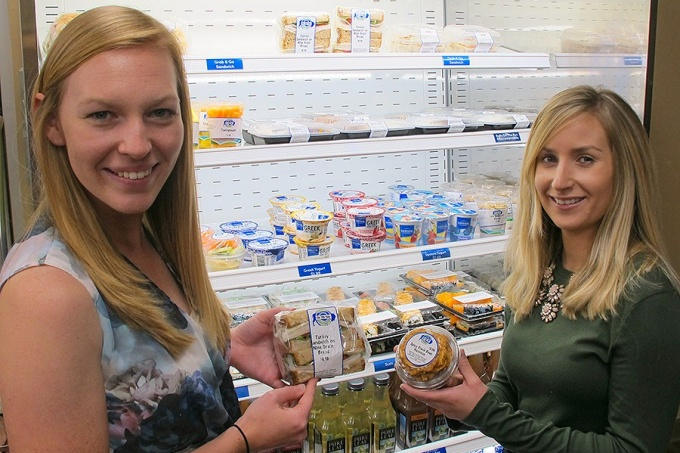 Kaitlyn Summers and Lori Bendersky show off two Grab n' Go items that were recently modified to reduce sodium levels