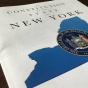 "Booklet entitled ""The Constitution of the State of New York"" featuring an graphic of the state of New York and the state's seal."