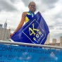 Patricia Lorquet, with the skyline of NYC in the background, holds a 4K for Cancer flag.