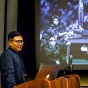 Marcus Yam (standing at a podium with one of his photographs projected on a screen behind him) discussed his path from being an aerospace engineering student to a Pulitzer Prize winning photographer during talks he delivered on Friday.