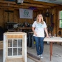 Jackie Hausler standing with two projects in her garage workshop.