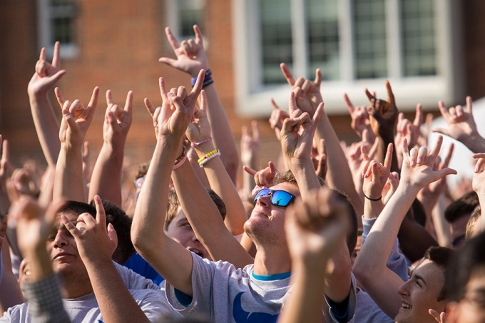 "Students gathered in a large group making the ""horns up"" hand sign"