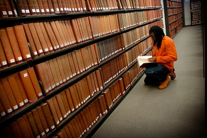 Student kneeling, looking through a book in front shelves of books in the law library.