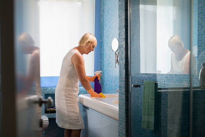 Active senior woman doing chores in the bathroom at home, cleaning wash basin and tap with spray detergent.
