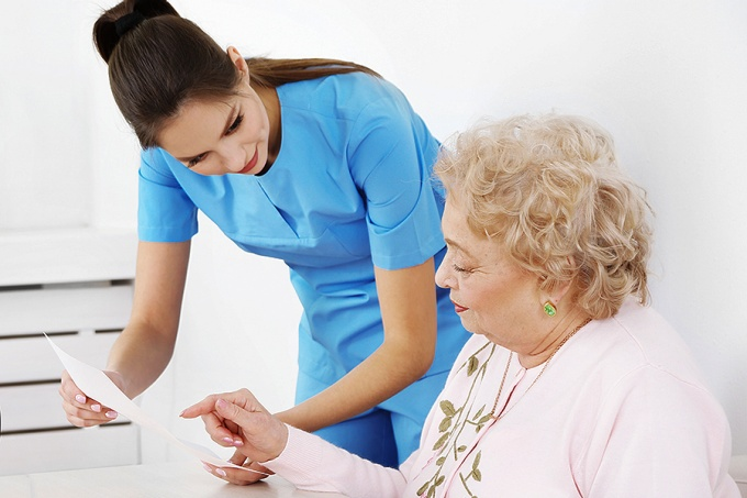 A nurse reviews health records with an elderly patient.