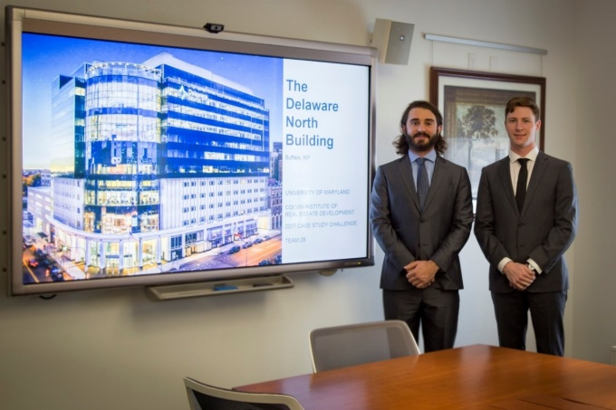 UB real estate development master's students Christopher Tringali and Kevin Turner standing next to a screen with their presentation on the Delaware North building.