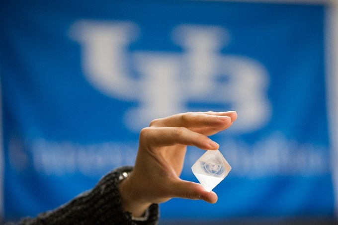 A judge holds up one of the crystals submitted for the crystal-growing contest in front of a large UB banner.