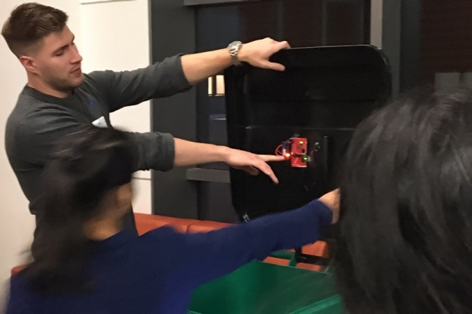 "Engineering student demonstrates the sensor on a ""smart"" recycling tote."