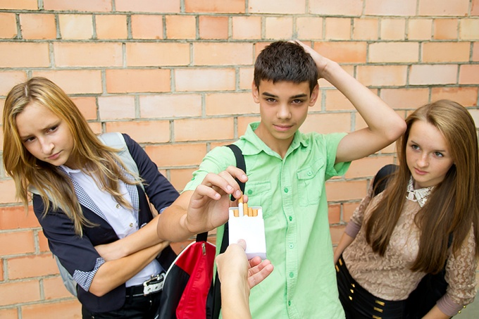 A teenage boy thinks about taking an offered cigarette while two teenage girls look on with skepticism.