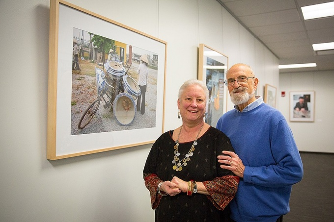 Jeannette Ludwig and Claude Welch standing by their photographs on exhibit in Silverman Library