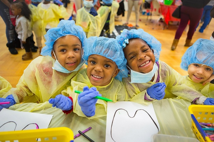 three smiling kids at give kids a smile day wearing bouffant hair covers and purple latex gloves