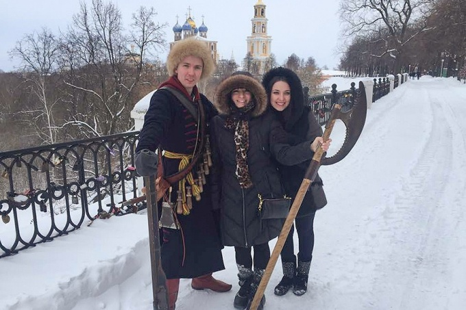 Molly Anderson (center) poses in frot of the Kremlin in Kyazan on a winter day.