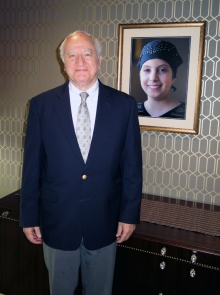 Allen Barnett, co-founder of Athenex, in Athenex's boardroom with a portrait of his granddaughter Carly, whom he lost to brain cancer.