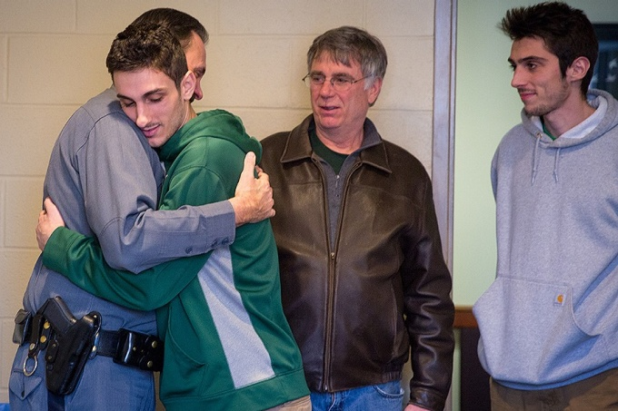 John Miske hugs Lt. David Urbanek as his father Peter Miske and brother Ryan look on.