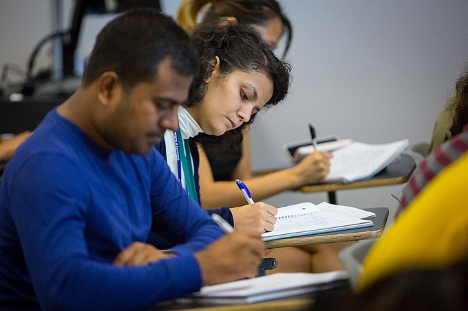 Diverse students take notes during a class.