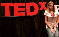 Lauren McGowen poses next to the TEDx letters.