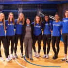 Kathy Twist poses with members of the women's volleyball team.