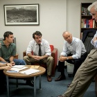 "Scene from ""Spotlight"" featuring Boston Globe Spotlight reporters meeting in an office setting."