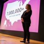 UB MBA student Lauren Weiss stands on stage for the pitch contest, with a map of the USA noting 7M people are blind or visually impaired projected behind her