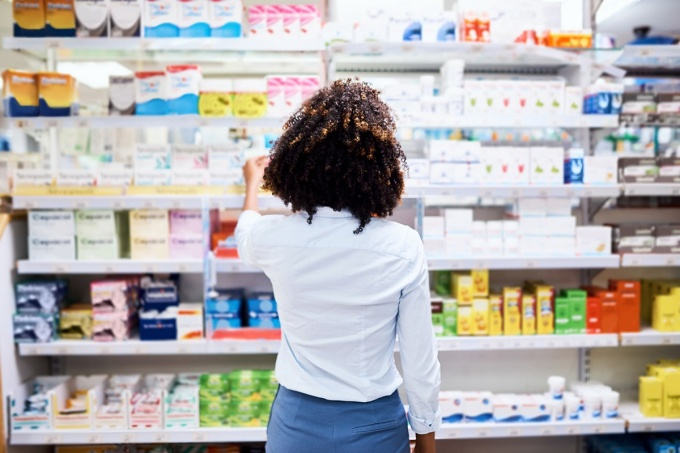 Photo of a woman in a pharmacy selecting a product from the shelf.