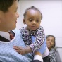 Toddler, who's mother participated in a clinical trial, is held by the doctor who conducted the trial.