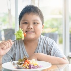 Obese boy enjoys eating vegetable salad, diet and healthy food concept.