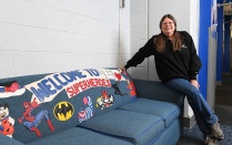 Portrait of Maureen Matesic seated on the arm of a sofa she re-upholstered that feature various superheroes.