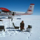 Beata Csatho makes gravity measurements on the Greenland Ice Sheet. Small plane is in the background