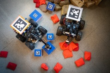 robots use their robotic arms to lift small blocks and bean bags.