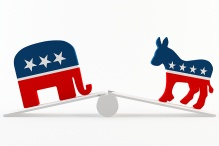 symbols for democratic and republican parties at opposite ends of a teeter totter.