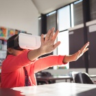 Schoolgirl gesturing while using virtual reality glasses in a classroom.