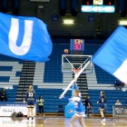 "Still from the ""Introducing UB's Center for Sports Advancement"" video of two cheerleaders running with giant ""U"" and ""B"" flags."