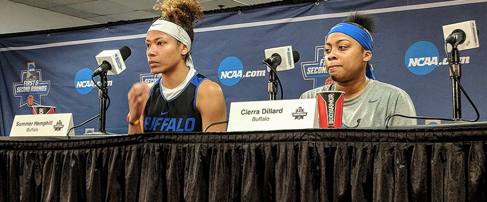 Summer Hemphill and Cierra Dillard sit at a skirted table and take questions from the media