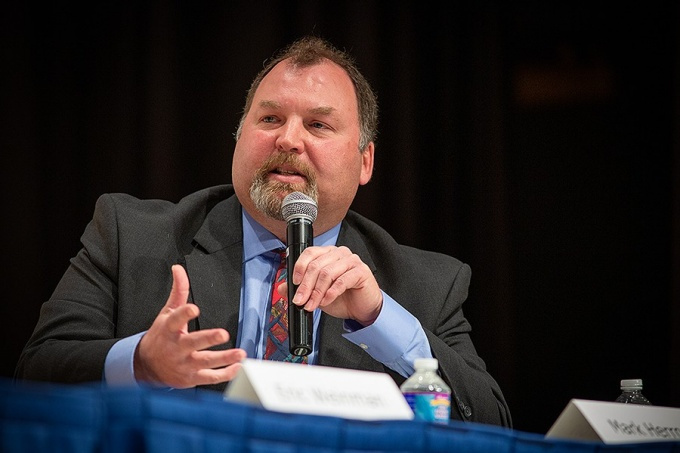 Mark Herron, holding a microphone and seated at a table during the Data Privacy Forum panel discussion, gestures as he makes a point.