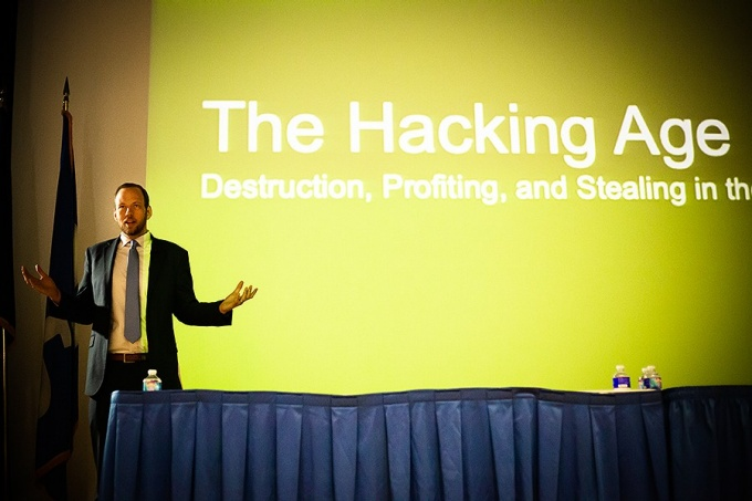 "Data security expert David Kennedy, stands on stage in front of a large screen reading, ""The Hacking Age. Distruction, Profiting, and Stealing in the [rest is cut off].""."