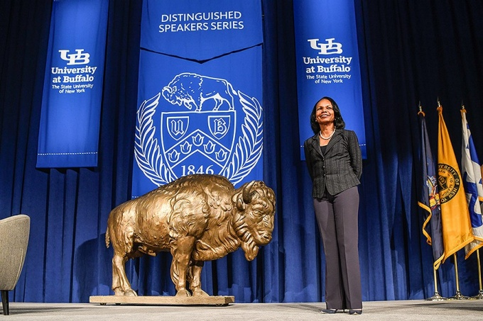 "Condoleezza Rice stands on stage next to a golden colored buffalo and under banners that bare the interlocking UB logos, the UB Seal and the words ""Distinguished Speakers Series.""."
