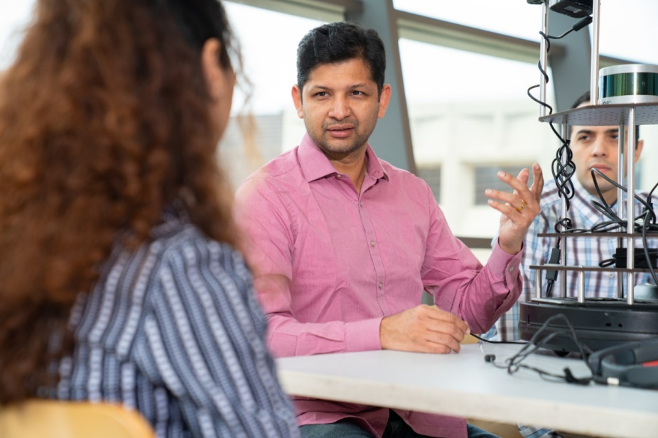 Karthik Dantu talks with a student in the lab.