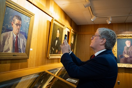 Daniel Mulhall, Ambassador of Ireland to the United States, photographs a portrait of James Joyce that is part of the UB James Joyce Collection.