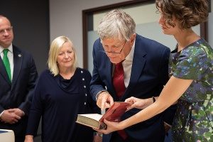 Daniel Mulhall, Ambassador of Ireland to the United States, examines a book that is part of the UB James Joyce Collection.
