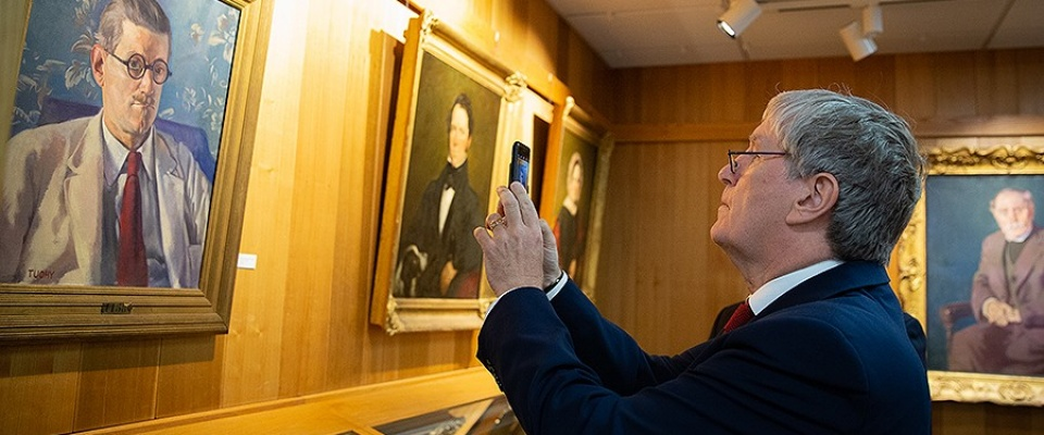 Irish Ambassador Daniel Mulhall takes a photo with a cellphone of a portrait of James Joyce in UB's Special Collections.