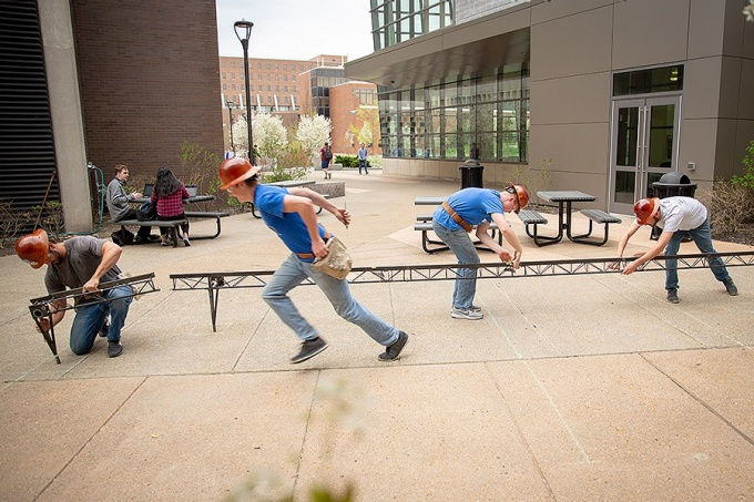 Students with the UB chapter of the American Society of Civil Engineers (ASCE) practice building their steel bridge in the Stevens Courtyard between Davis and Jarvis halls.