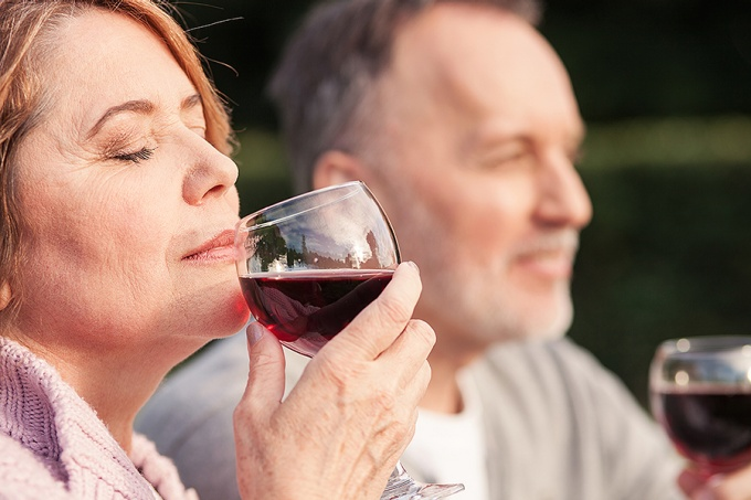 Woman with eyes closed sniffing a glass of red wine.