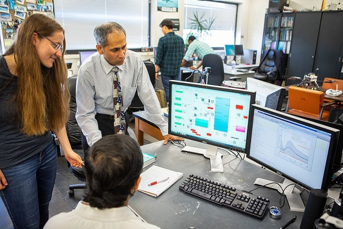 Tarunraj Singh and his students look at computer screens in the lab.