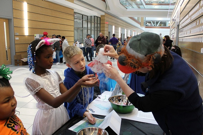 Three children dressed in Halloween costumes take part in a dry ice demonstration that teaches them about the environment on Mars at a table manned by staff from the Buffalo Museum of Science.