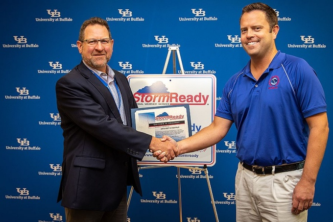 Michael Fries (right), with the National Weather Service, presents Jay Roorbach with a sign acknowledging that the University has earned the distinction of being a StormReady University in October 2019.
