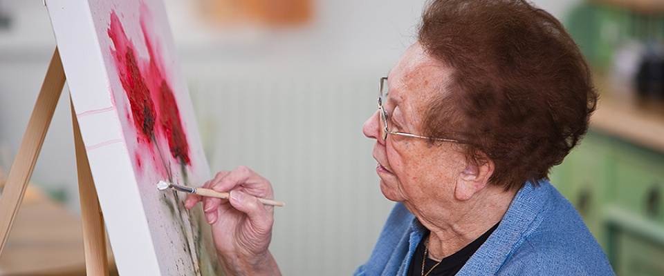 Older woman painting on a canvas.