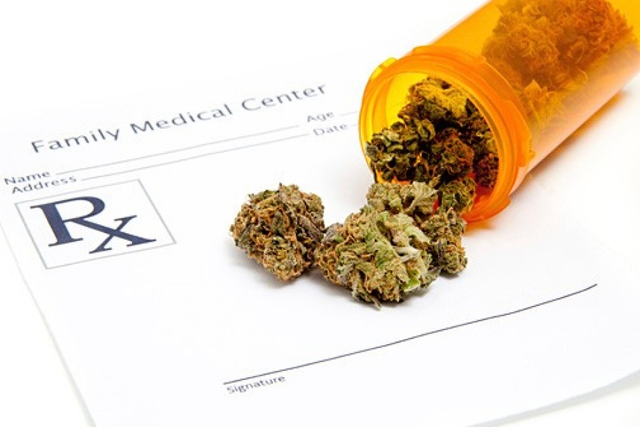 pill bottle full of marijuana buds lays sideways on a prescription pad.