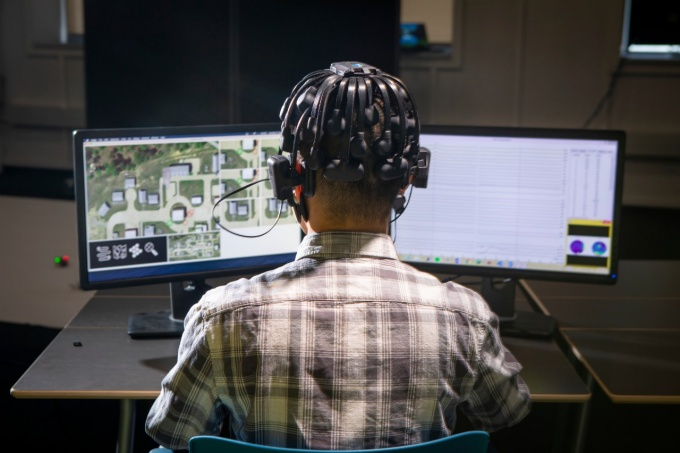 Student wearing headgear to measure brain waves is playing a video game at a computer.