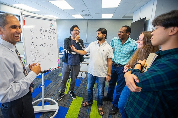 Professor Taraunraj Singh, with mechanical and aerospace engineering, works with students in a research lab in Furnas Lab in September 2019.